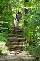 Family walking down stone steps in woods
