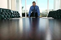 Businessman Leaning over Conference Table