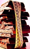 Measure tape around tall stack of chocolate bars