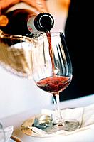 Red wine being poured into glass from bottle