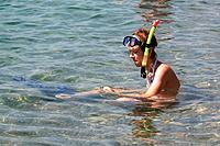 Young woman sitting in water with snorkel and fins