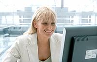 Smiling Businesswoman Looking at Computer Screen