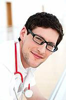 Germany, Bavaria, Diessen am Ammersee, Close up of young doctor leaning on railng with sethoscope, smiling, portrait