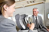 Germany, Bavaria, Munich, Businessman and woman toasting champagne in business class airplane cabin, smiling