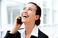 Germany, Bavaria, Diessen am Ammersee, Young businesswoman talking on mobile phone, laughing, close up