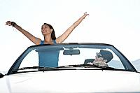 Spain, Majorca, Young man driving and woman standing in cabriolet car