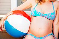 Pregnant woman holding a beach ball
