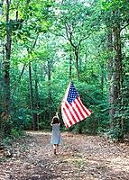 Little girl carrying an American flag through the woods