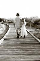 Brother and sister walking along wooden beach path