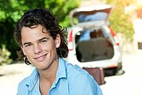 Italy, Tuscany, Close up of young man and car with luggage in background