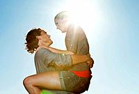 Italy, Tuscany, Young man carrying woman against sun