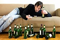 Germany, Hessen, Frankfurt, Drunk man lying on sofa with empty beer bottles