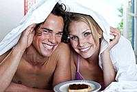 Italy, Tuscany, Young couple lying with bedsheet on bed in front of jam and bread