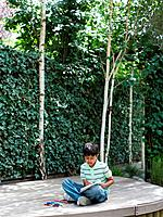 Boy drawing in garden