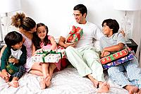 A family in bed with gifts