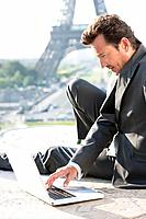 Businessman working on a laptop with the Eiffel Tower in the background, Paris, Ile_de_France, France