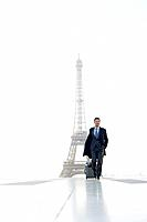 Businessman walking with luggage with the Eiffel Tower in the background, Paris, Ile_de_France, France