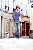 Man holding a dog on leash, Paris, Ile_de_France, France