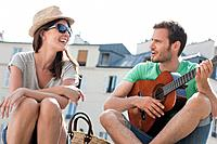 Man playing a guitar with a woman smiling, Canal St Martin, Paris, Ile-de-France, France (thumbnail)