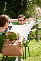 Man sitting in a garden and looking at a laptop, Paris, Ile_de_France, France