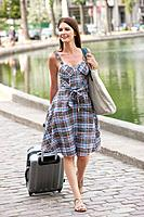 Woman pulling a suitcase and smiling, Paris, Ile_de_France, France