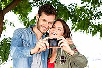 Couple taking a picture of themselves with a digital camera, Paris, Ile_de_France, France