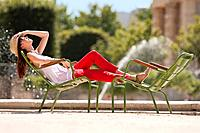 Woman resting in a chair near a pond, Bassin octogonal, Jardin des Tuileries, Paris, Ile-de-France (thumbnail)