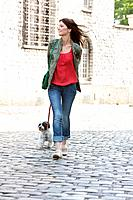 Woman holding a puppy on leash, Paris, Ile_de_France, France