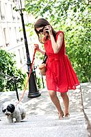 Woman holding a puppy on leash and talking on a mobile phone, Montmartre, Paris, Ile_de_France, France