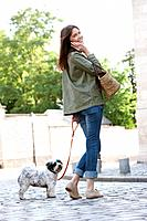 Woman holding a puppy on leash while talking on a mobile phone, Paris, Ile_de_France, France