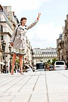 Woman hailing a taxi, Paris, Ile_de_France, France