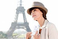 Woman holding a guide book with the Eiffel Tower in the background, Paris, Ile_de_France, France