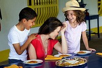 Mother and children eating dinner