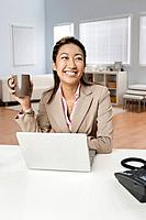 Mixed race businesswoman drinking coffee at desk