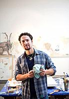 Mixed race artist cleaning paintbrush in studio