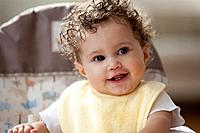 Smiling mixed race baby girl sitting in highchair