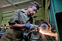 Caucasian man grinding metal in workshop