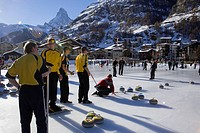 Group of men curling on a rink, Matterhorn in background, Zermatt, Valais, Switzerland Curling: A rink game where round stones are propelled by hand o...