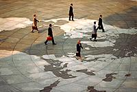 Businesspeople walking across world map