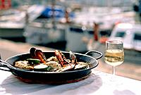 Paella and a glass of white wine with a harbour in the background