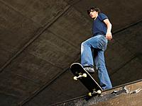 Teenage boy waiting at top of ramp with skateboard
