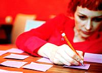 Businesswoman writing adhesive notes on desk
