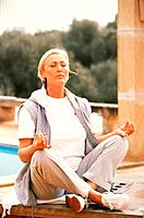 Senior woman in lotus position outdoors