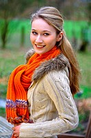 Smiling young woman wearing scarf and pullover outdoors