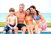 Family on edge of swimming pool