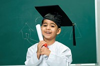 Boy 4_5 wearing mortarboard and holding degree, portrait