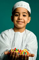 Boy 8_9 years holding colorful alphabets, smiling, portrait