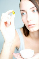 young woman looking at capsule