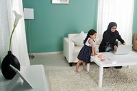Arab mother working at home, daughter playing