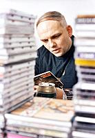 Man behind piles of cds
